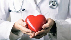 egy orvos egy nagy piros szívet tart a kezében