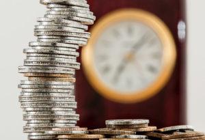 pénzérmék egy ketyegő óra mellett