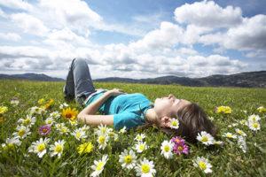 virágokkal teli mezőn fekvő lány